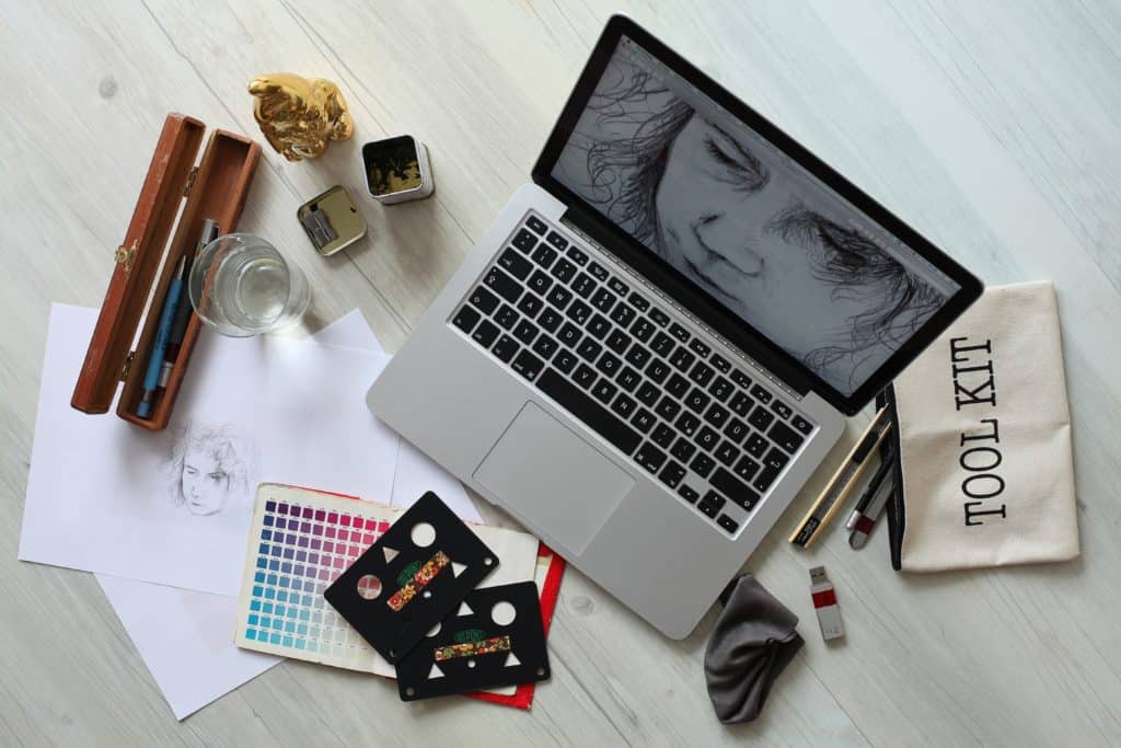 Essential items for creatives includes a laptop, pencils, papers, color guides