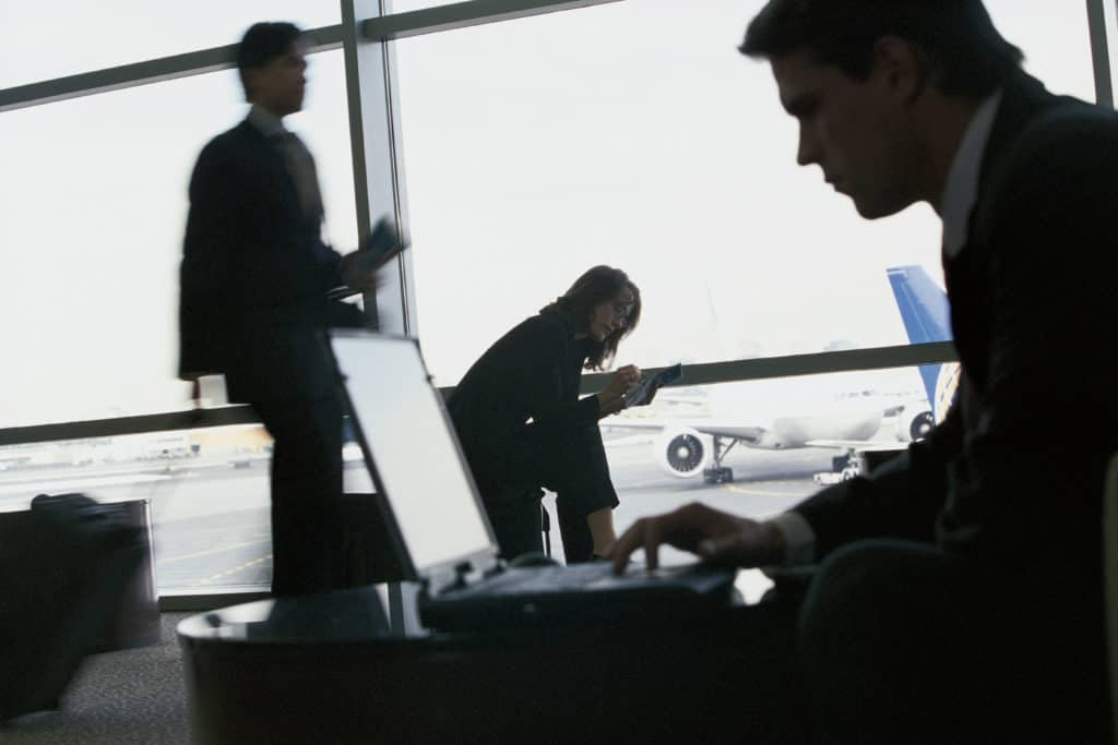 Man using his laptop at the airport before having his baggage checked