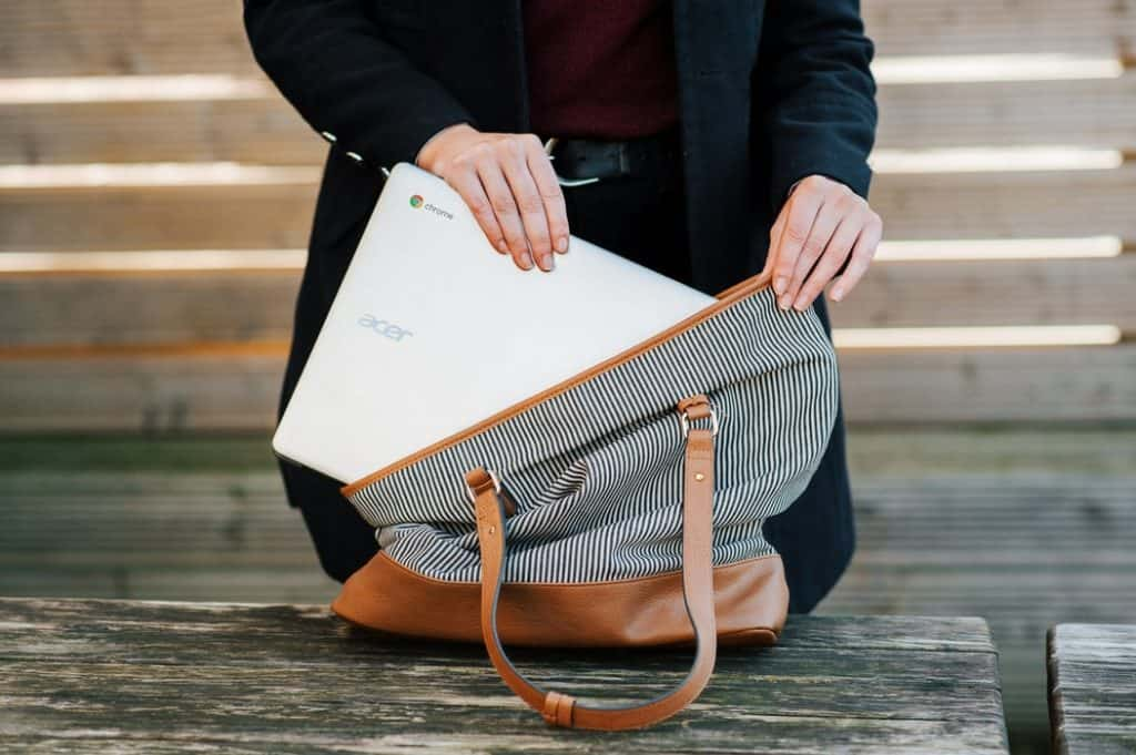 Woman putting a laptop in a bag