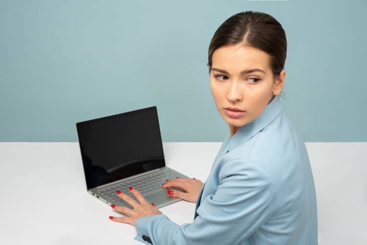 Woman with her hands hovering on her laptop wondering if she can upgrade her RAM