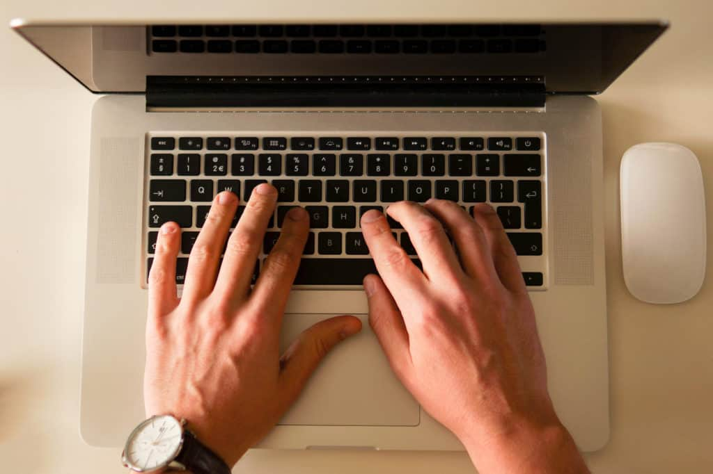 A close up of a person with both their hands on a keypad of a laptop