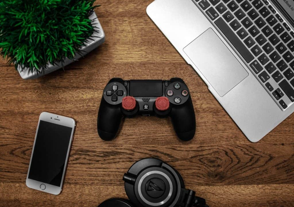 Laptop, PS4 controller, phone and headphones on wooden table