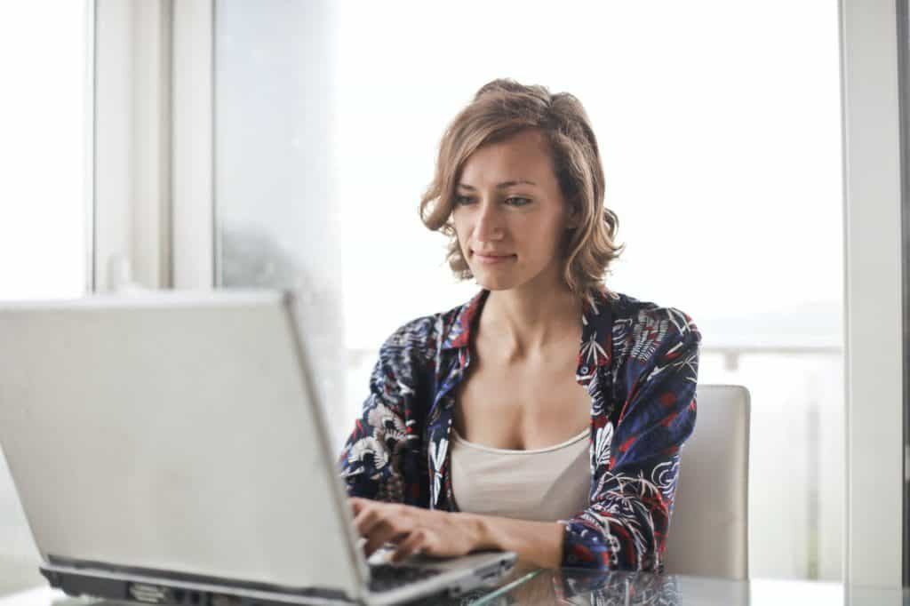 Woman sitting while using while a laptop