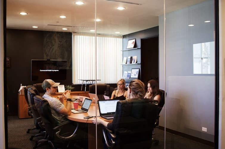 Group of people using their laptops while at a work meeting