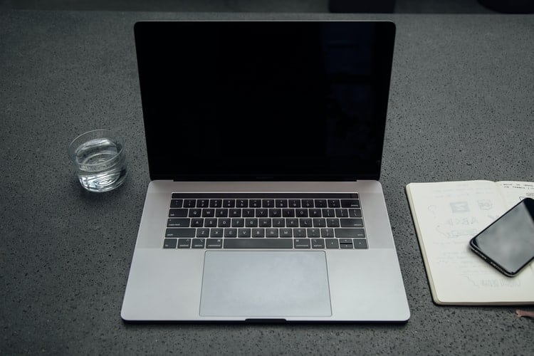 A silver laptop right beside a glass of water, notebook and mobile phone