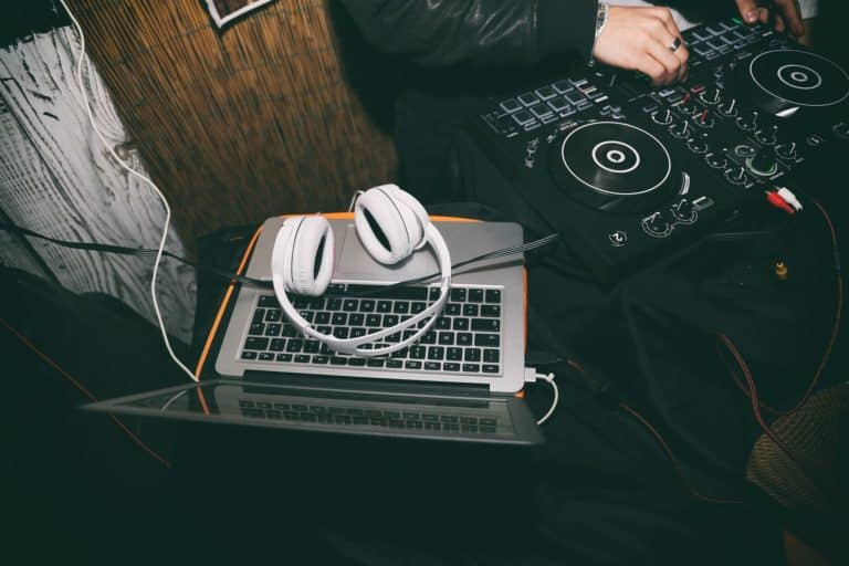 Headphones on top of a laptop being used with a dj software in a club