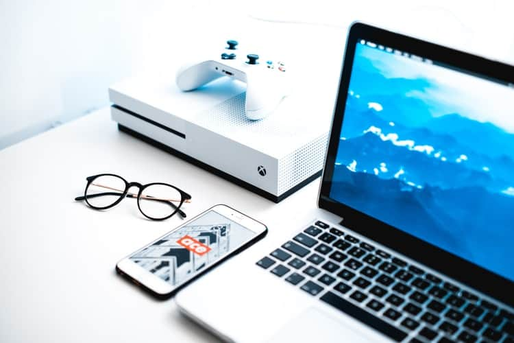 Laptop beside a mobile phone, glasses and a game console