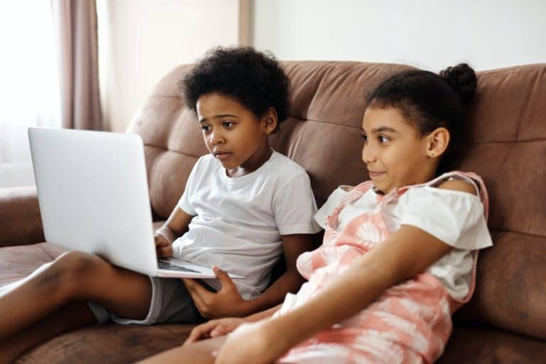 Two kids sitting on the couch playing a game on a laptop