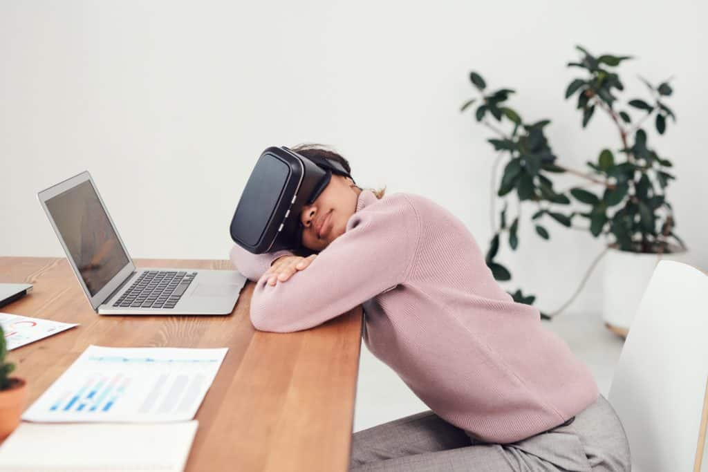 Woman sleeping in front of her laptop while wearing an Oculus Rift VR head gear