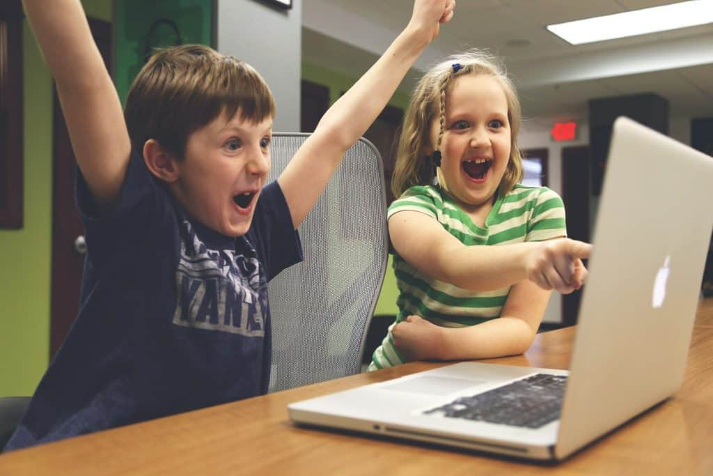 Two children celebrating their win while playing a game with their laptop