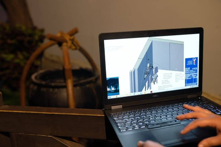 Person using SketchUp on a laptop to create a 3D diagram for a project