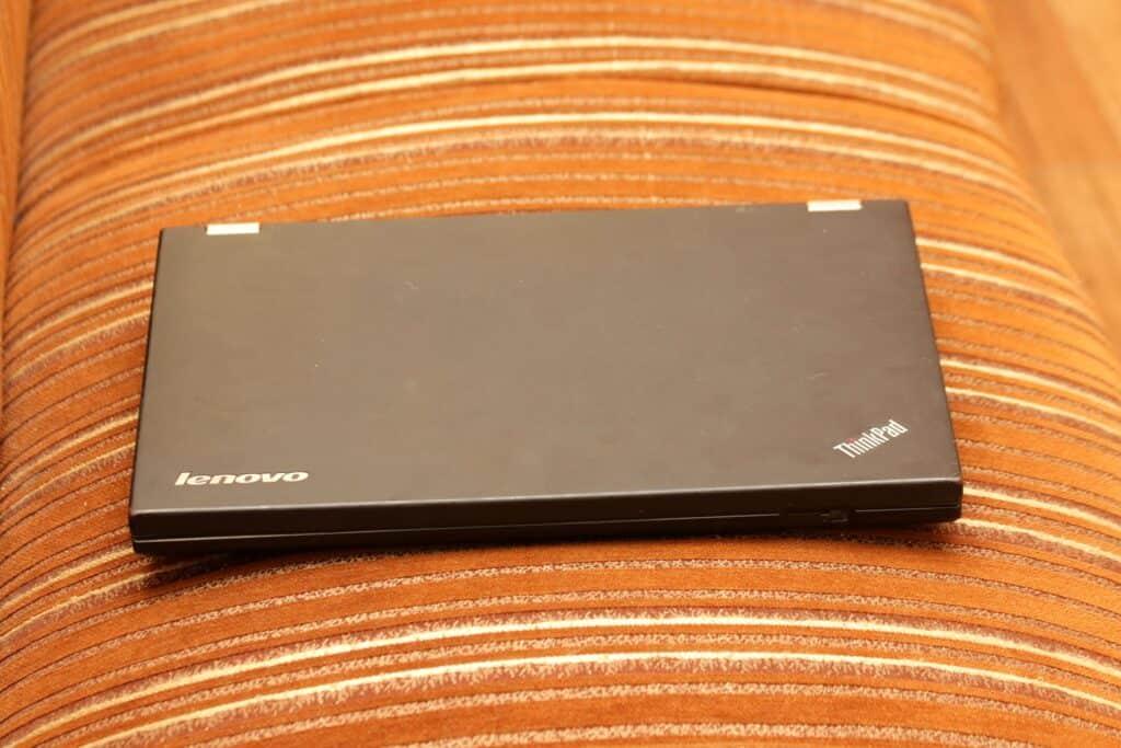 Closed Lenovo laptop on an orange sofa chair