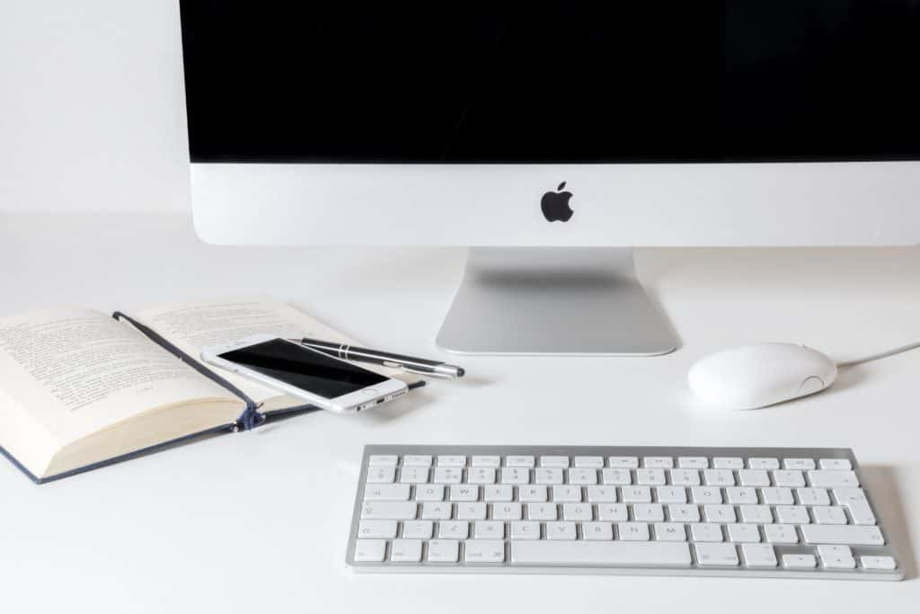 A white iMac desktop with a wireless keyboard, mouse, and an opened book with a mobile phone beside it