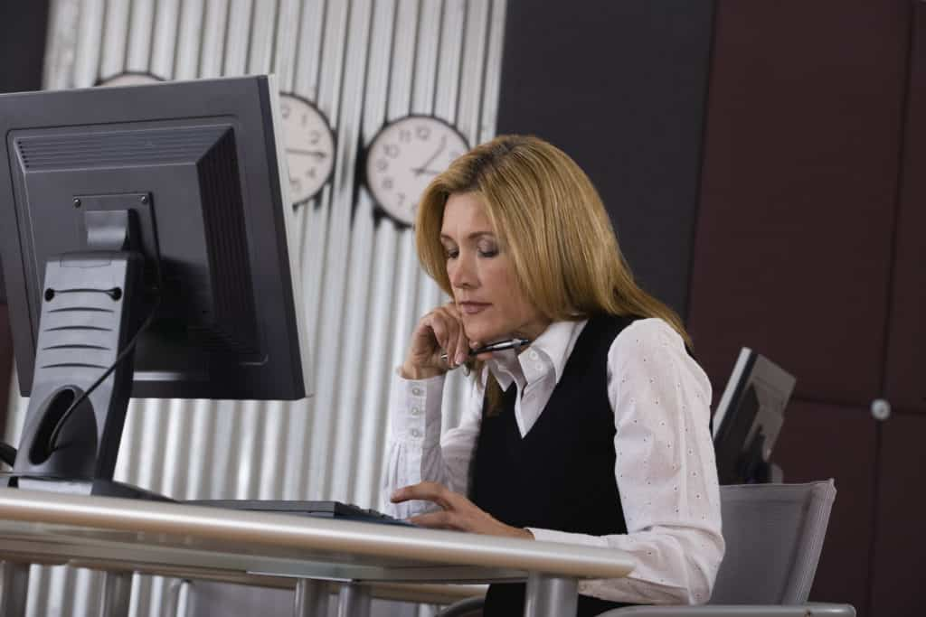 Woman looking at her keyboard while using her desktop at her office