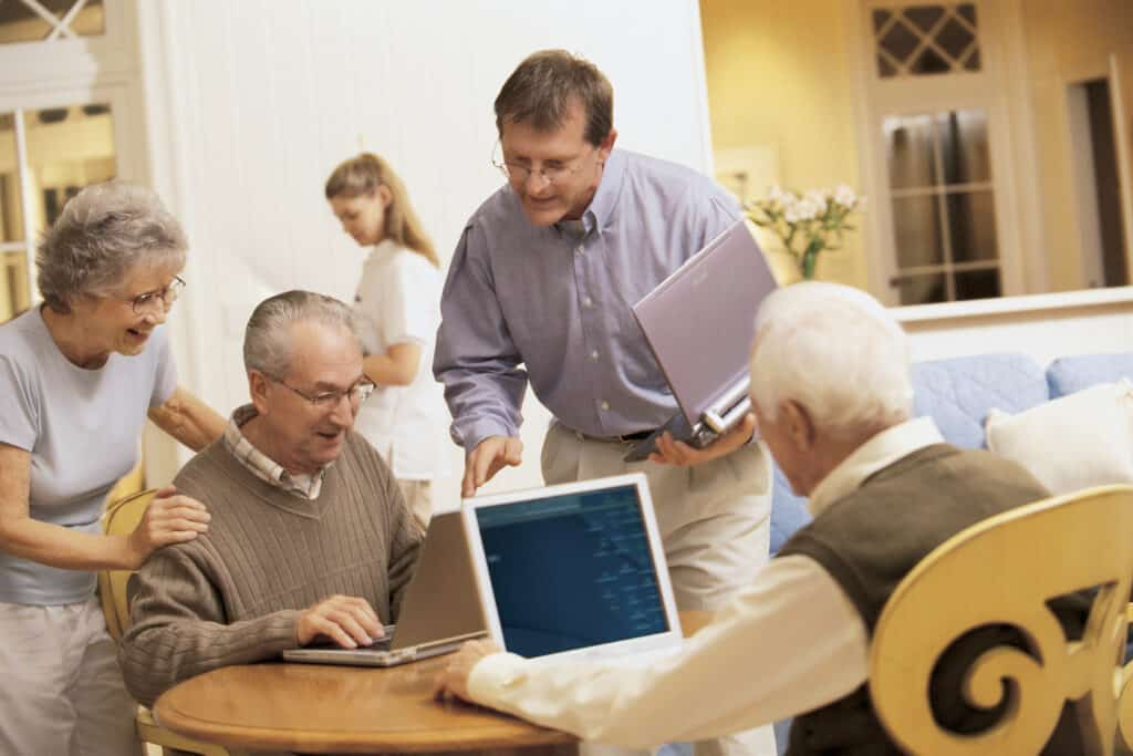 Senior citizens trying to help each other with using their laptops
