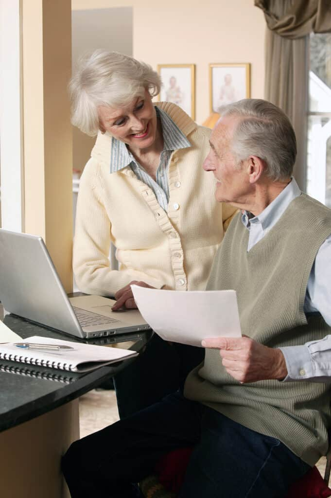 Senior citizen couple using their laptop for their home needs