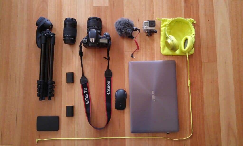 Asus laptop beside a Canon camera, headphones, and other accessories