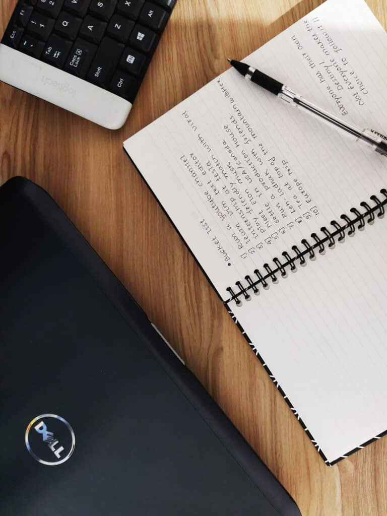 Opened notebook beside a Dell laptop